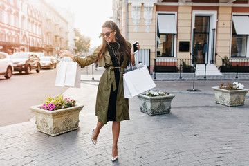 Full-length portrait of amazing woman in sparkle shoes and green coat carrying packages and smiling. Photo of slim happy girl in sunglasses hurrying home after shopping, walking by flowerbed.