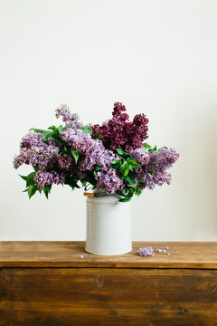 Purple bouquet of lilac flowers in a stylish vase on wooden table