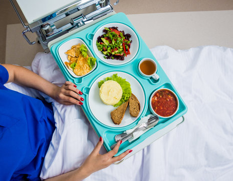 Tray with breakfast for the young female patient. The young woman eating in the hospital.