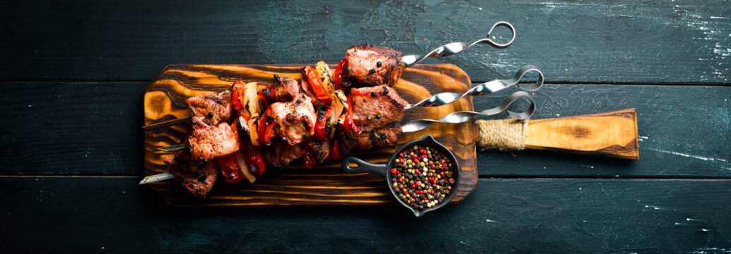 Shish kebab BBQ meat with onions and tomatoes. On a black background. Top view. Free space for your text. Rustic style.