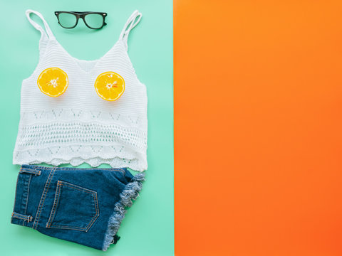 summer clothes concept from Women's Clothing, Denim shorts, Camisole, Sunglasses and Half cut orange, flat lay on red and green background pastel color for advertising sale products.