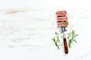 Juicy Steak on the fork with herbs and spices. Top view. Free space for your text.