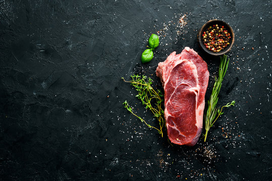 Raw Steak Ribeye. On a black stone table. Top view. Free space for your text.