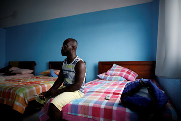 A migrant from Ghana watches television in his room in a hotel in Tapachula