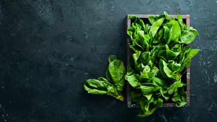 Fotomurales - Spinach in a wooden box. Healthy food. Top view. Free space for your text.
