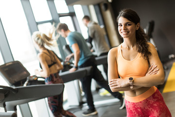 7034d48831746c Smiling sporty young woman standing with arms folded and looking at camera  at the gym