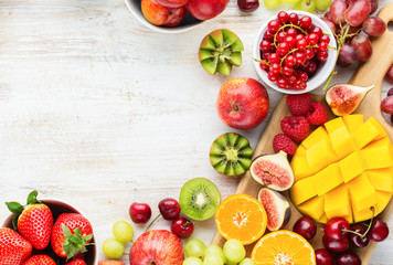 Wall Mural - Colorful fruits background, cut mango, strawberries raspberries oranges plums apples kiwis grapes blueberries cherries, on white table, copy space, top view, selective focus