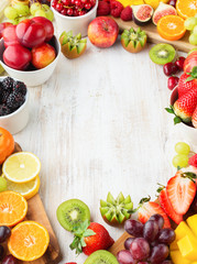 Wall Mural - Healthy raw background, cut fruits, strawberries raspberries oranges plums apples kiwis grapes blueberries mango persimmon, on white table, copy space in the middle, selective focus