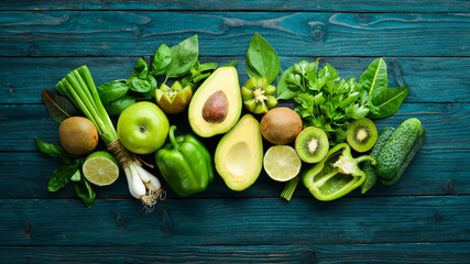Healthy Green food. Fruits and vegetables - avocado, lime, onion, apple, kiwi, spirulina. On a blue wooden background. Top view. Free space for your text.