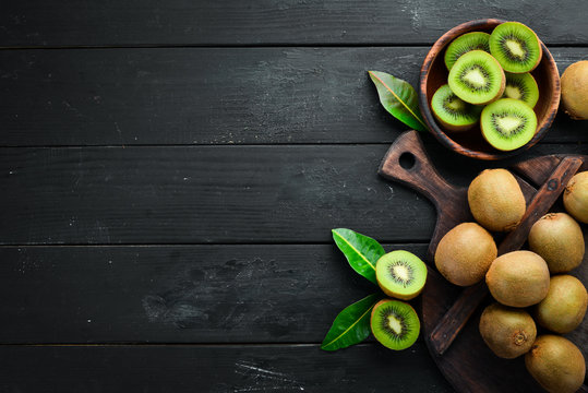 Fresh kiwi and green leaves on the table. Rustic style. Fruits. Top view. Free space for text.