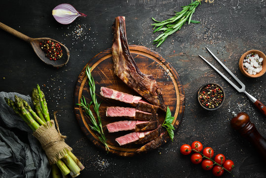 Grilled steak on the bone, herbs and spices on a wooden background. Barbecue. Top view. Free space for text.