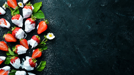 Strawberry with cream on a black stone background.
