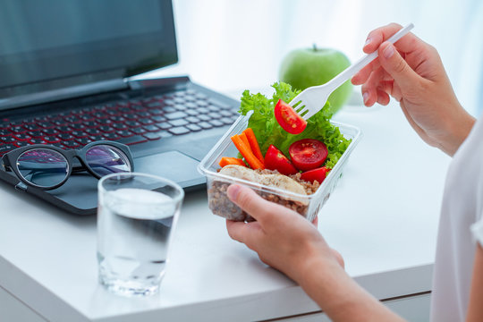 Healthy snack at office. Woman eating food from take away lunch box at workplace during lunch break. Container food at work