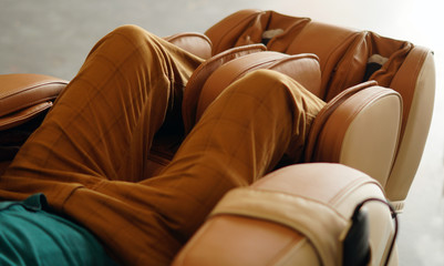 Closeup of legs of a man relaxing on the electric massage chair