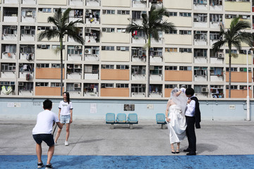 Couples take photos in front of Choi Hung estate, an apartment complex that became famous because of the rainbow color paints in Hong Kong