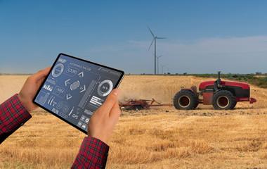 Etiqueta Engomada - A farmer with digital tablet controls an autonomous tractor on a smart farm