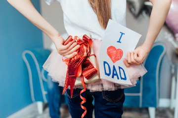 I love you, dad! Closu up photo of small girl holding presents for dad.. Happy Father's Day!