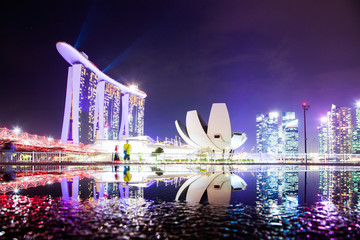 Fototapeta SINGAPORE, SINGAPORE - MARCH 2019: Skyline of Singapore Marina Bay at night with Marina Bay sands and Art Science museum reflecting in a pond after rain. Vibrant night scene