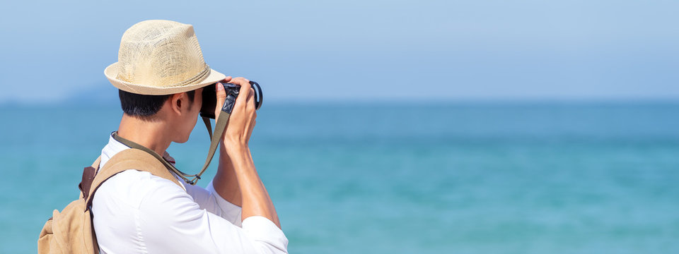 Candid of young attractive asian man hold camera taking photo in blue sky and sea view background. Happy asian hipster male photographer in youth freedom culture lifestyle travel in rear view concept.