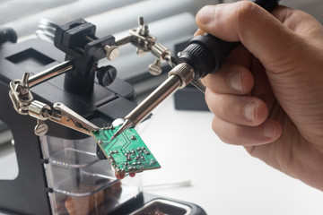 Electronics engineer repaired with soldering using soldering station and other components Wall mural