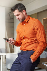 Businessman using his mobile phone and text messaging while sitting at office desk