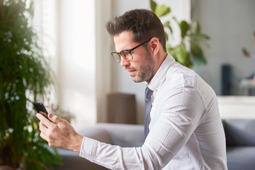 Businessman text messaging while sitting in the offce