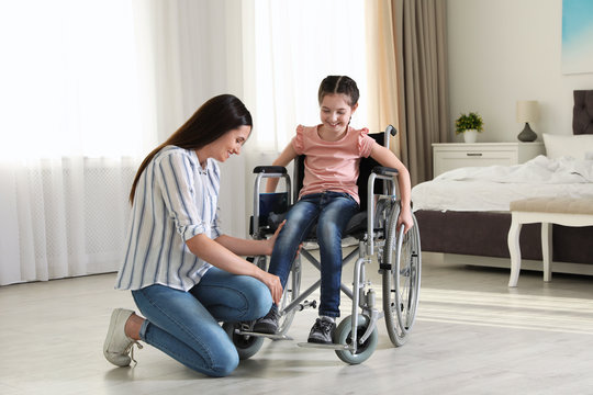 Young woman helping her disabled daughter get in wheelchair at home