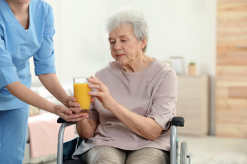 Nurse giving glass of juice to elderly woman in wheelchair indoors. Assisting senior people