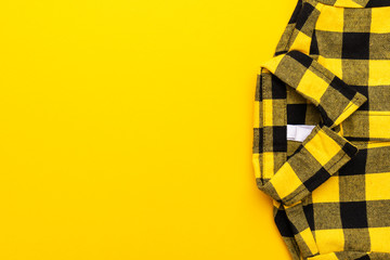 yellow and black checkered shirt on the yellow background. top view of yellow shirt with copy space.