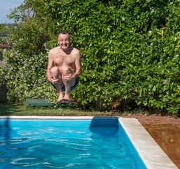 Caucasian man takes a bomb dive in the pool with a funny expression