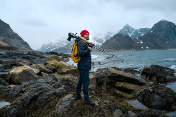 Young man photographer standing at rock in the mountains at Beach photographing the landscapes on Lofoten Islands in Norway. Fotobehang