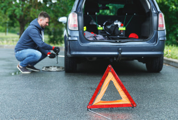 Warning triangle and man changing car wheel