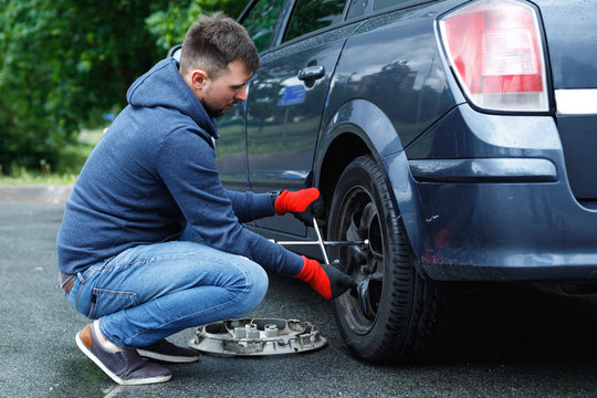 Young man changing flat tire on his car