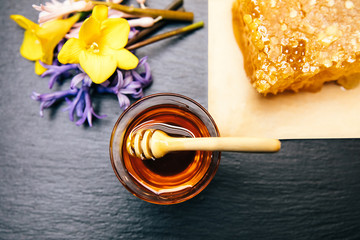 Healthy, natural, organic and sweet honey in glass jar or bowl with honey dipper, flowers and honeycomb on black background.