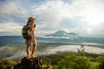 Woman enjoying sunrise from a top of mountain Batur, Bali, Indonesia.