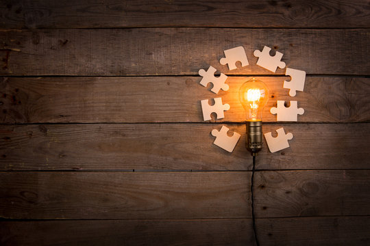 Idea and teamwork business concept, vintage incandescent light bulb and jigsaw on the wooden background