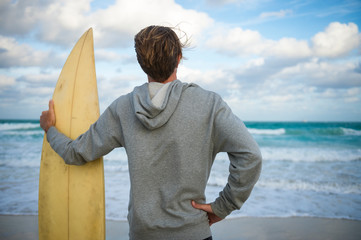 Surfer in gray hoodie holding his surfboard on the shore of a windy tropical beach