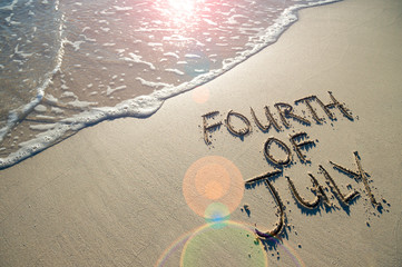 Fourth of July message written for the American Independence Day holiday in smooth sand with sunny lens flare view of an incoming wave on the beach