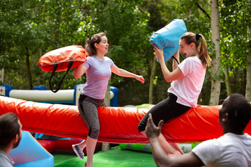 Women fighting by pillows on inflatable beam