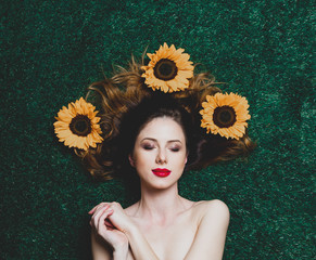 red-haired girl with sunflowers on grass