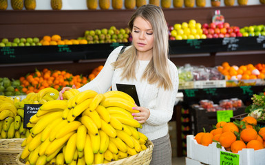 Young female  choosing fresh bananas on the supermarket