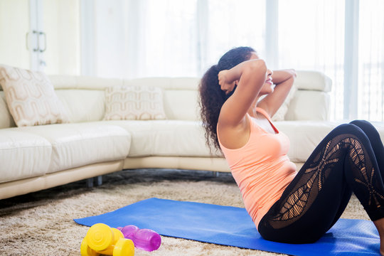 Young woman doing abdominal sit ups at home