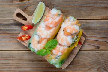 Fototapeta Top view of Vietnamese spring rolls with shrimps on wooden background obraz