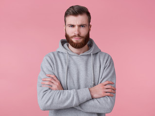 Portrait of young frowning handsome red bearded man in gray hoodie, stands with crossed arms, disapprovingly looks at camera, stands over pink backround.