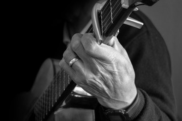 Foto op Aluminium Vechtsport Approach to the hand of an elderly man sitting holding a guitar with a wedding ring on his finger on a dark background. Black and white image