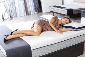 girl testing quality of new mattress