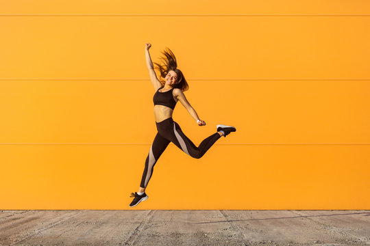 Young happy beautiful girl wearing black sporwear practicing sport exercises in morning on street, celebrate result of training, jumping full length, orange wall background, outdoor