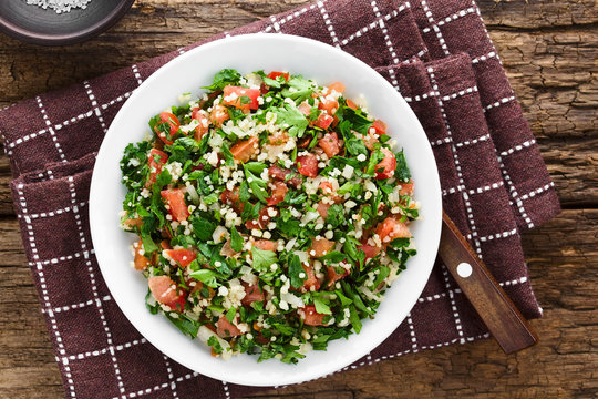 Fresh vegan Tabbouleh salad made of tomato, parsley, onion and couscous on plate, photographed overhead