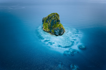 Aerial drone view of a beautiful secluded cliff island surrounded by azure turquoise blue ocean water. Bacuit archipelago is one of the best places for diving. El Nido, Palawan
