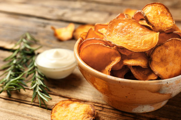 Delicious sweet potato chips in bowl, rosemary and sauce on table. Space for text